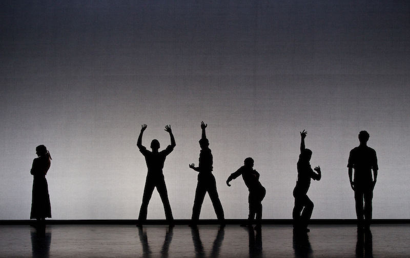 A group of dancers in silhouette. They're positioned at varying heights and assuming different poses. One figure is set apart with her arms crossed.