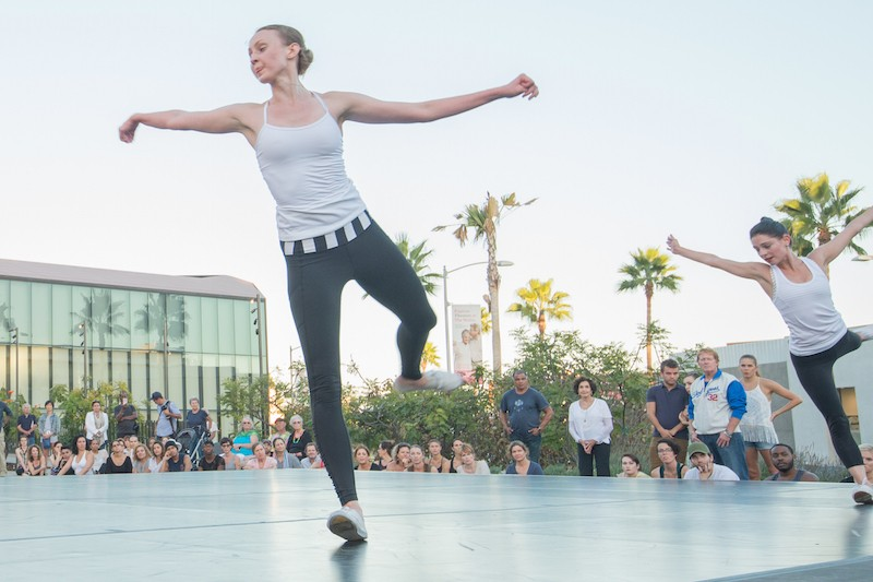 Kaitlyn Gilliland and Ramona Kelly dance on a stage outdoors before a crowd of people in LA