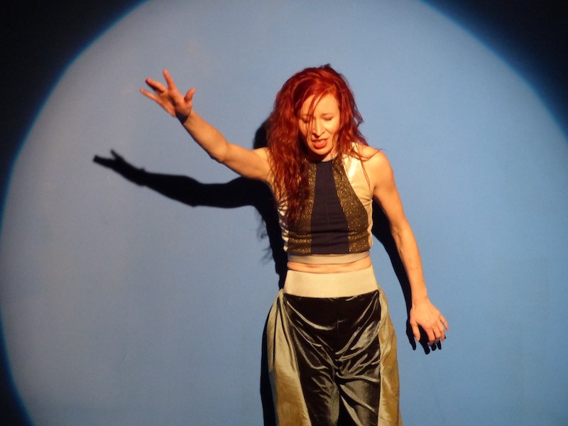 A woman in a silk tank top and flowy pants thrusts her arm out while standing in front of a blue wall. A spotlight illuminates her.