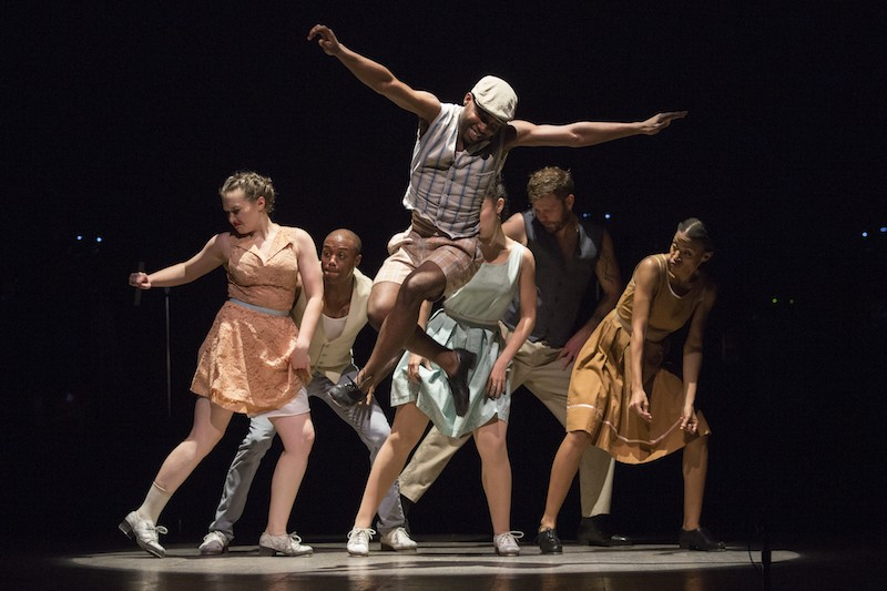 Byron Tittle, in shorts, a newsboy cap and vest jumps high into the air. The ensemble in mismatched dresses and vests stand behind in a clump with smirks on their faces.