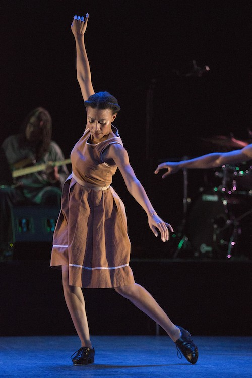 Karida Griffith in a organge dress stands on her right leg with her left toe dragging inwarm. Her arms make a diagonal; her right reaches high while her left reaches to the floor.