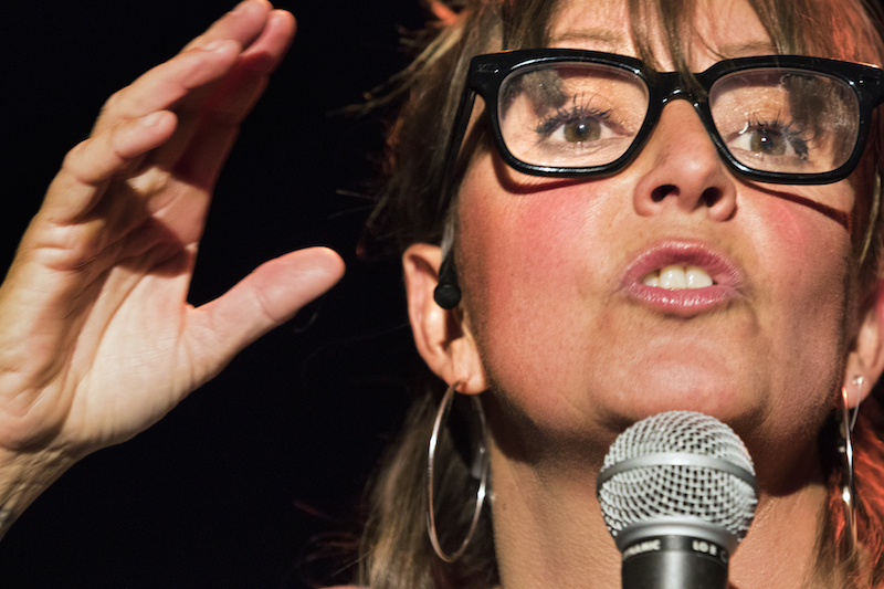 A close up of Truscott wearing black acetate eye glasses speaking into a microphone.