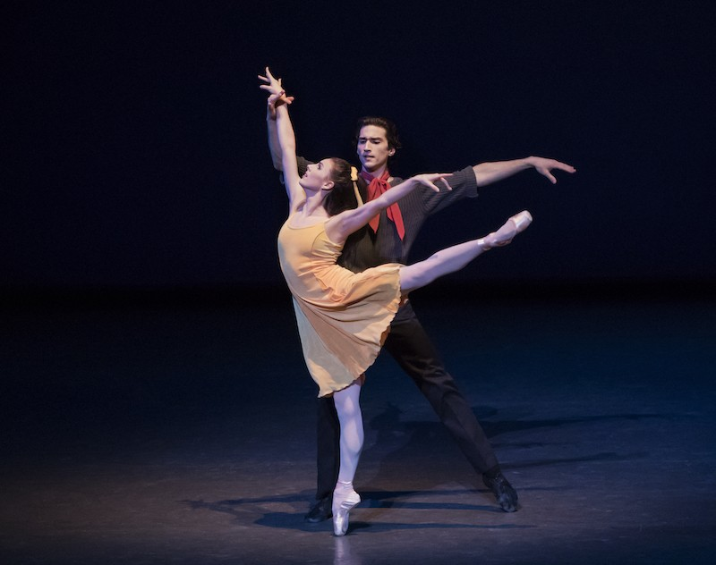 Tiler Peck in a yellow dress in a high arabesque en pointe. Zachary Catazaro holds her wrist and wears a red scarf around his neck.