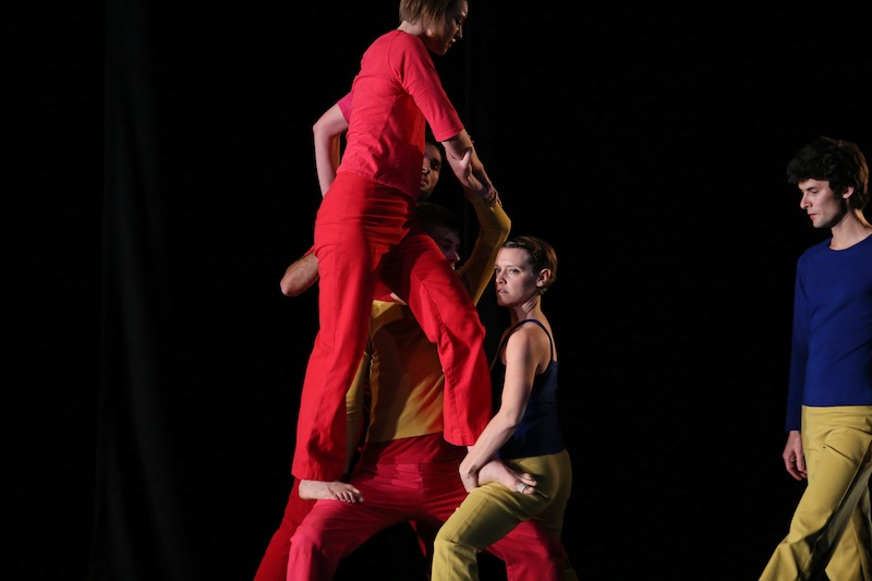 One dancer stands another's thighs as if she is she walking on air. One dark haired male dancer in blue and yellow observe