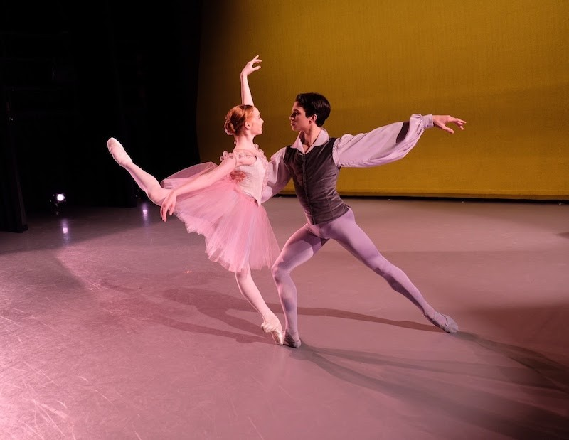 A woman in a pink tutu assumes a high attitude position en pointe that is slightly off kilter. Her male partner supports her back.