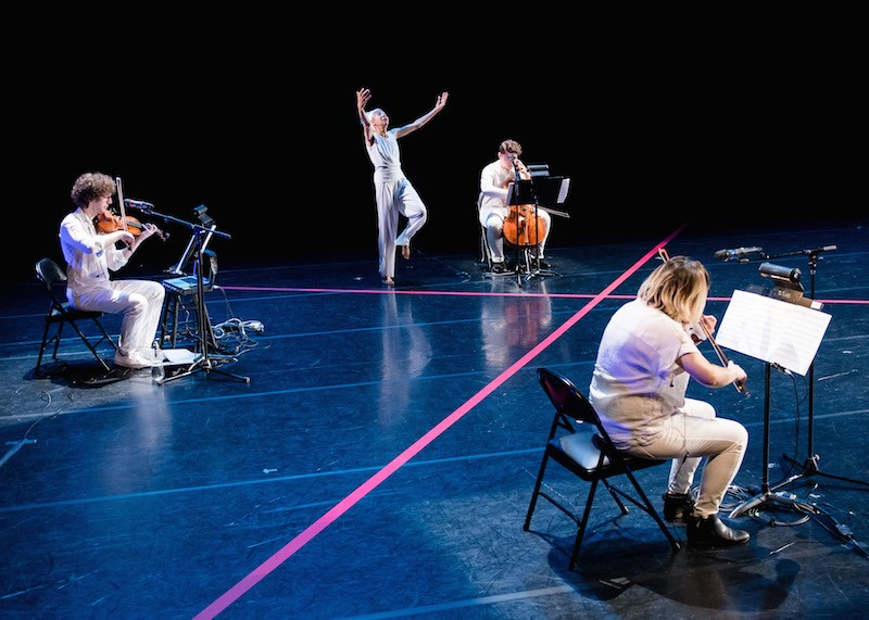 McIntyre dressed in white reaching her arms overhead while the string trio sits in chairs around her.Thick pieces of pink tape make an x on the stage