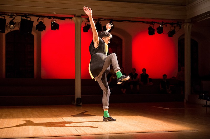 Caleb Teicher wears a black and yellow tunic, grey slacks, green socks and tap shoes. Both of his arms are stretched to the ceiling while one leg is hiked up in the air.