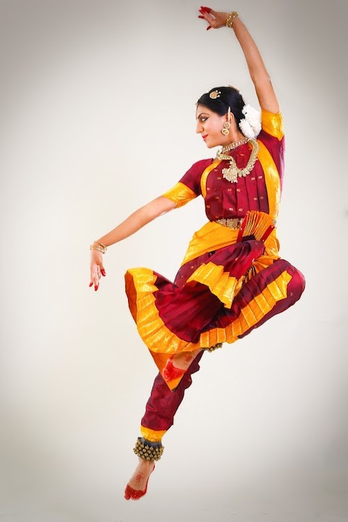 In a bright marigold and red costume, Srinidhi flies into the air