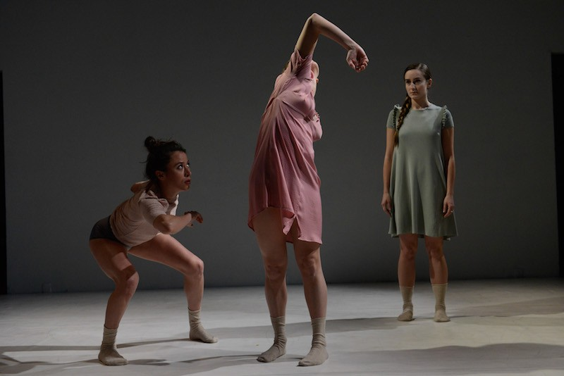 Three women in socked feet. One is crouching down and looking up at the center figure whose elbow is pointing up. Another dancer in the background watches.