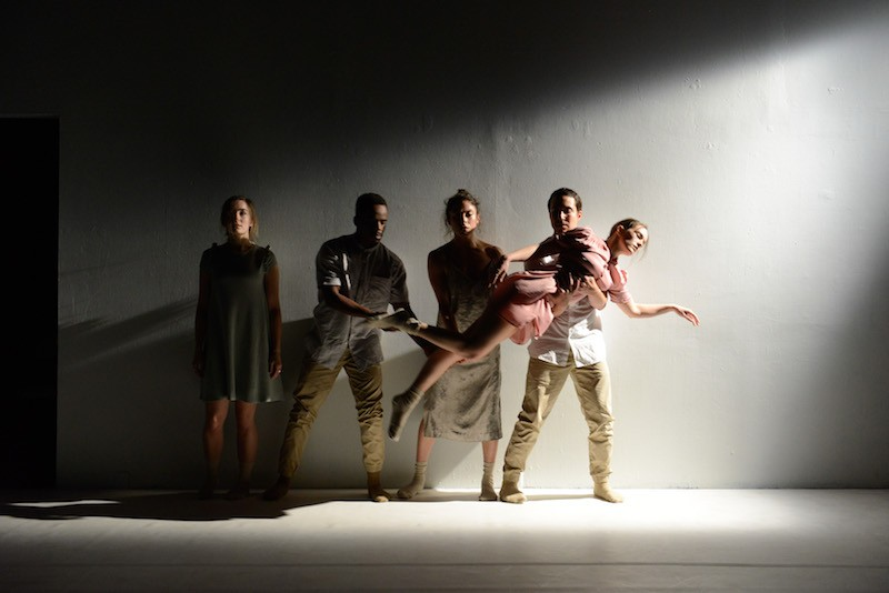 Four dancers stand against a white wall. They hold one women horizontally. She looks like she's floating.