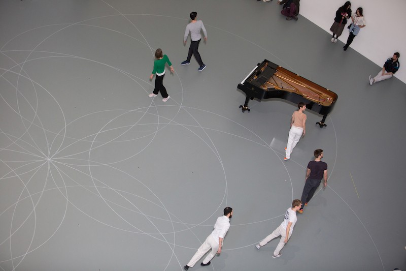 An aerial view of a group of dancers standing on one of the outlines of a circle. They all turn their heads over their shoulders. The piano is also set by them.