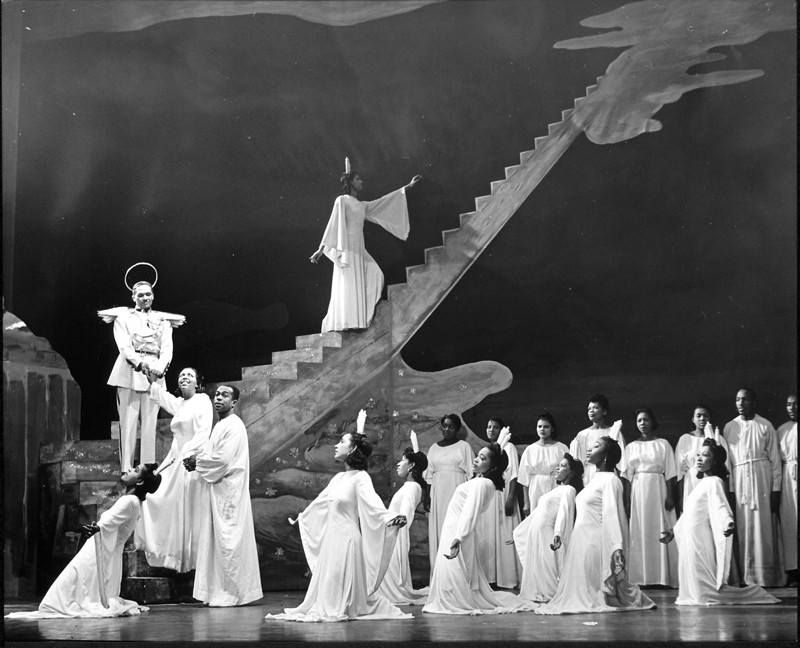 Black and White photo of the cast in the original 1943 Broadway production. The ensemble is dressed in all white robes while another cast member wears a halo and angel wings.