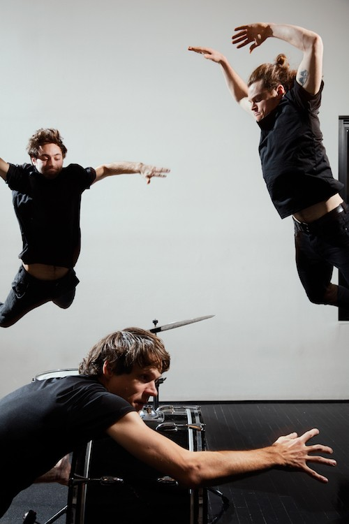 Two men jump into the air while their drummer hovers near his set