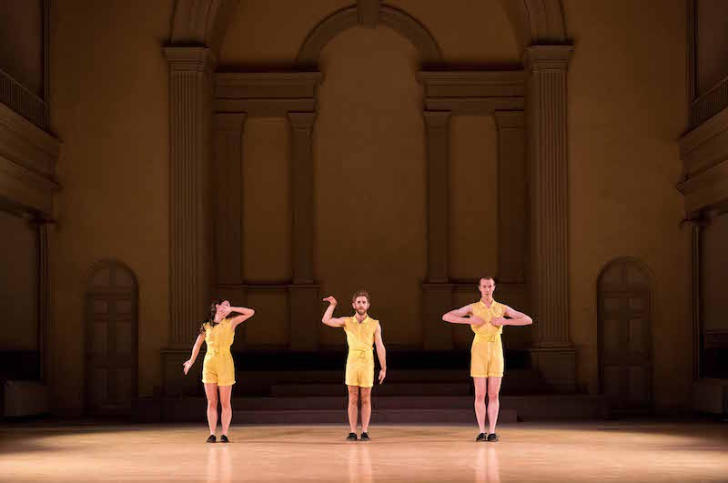 Three dancers in yellow rompers standing in a line. Their arms cover their face or eyes.