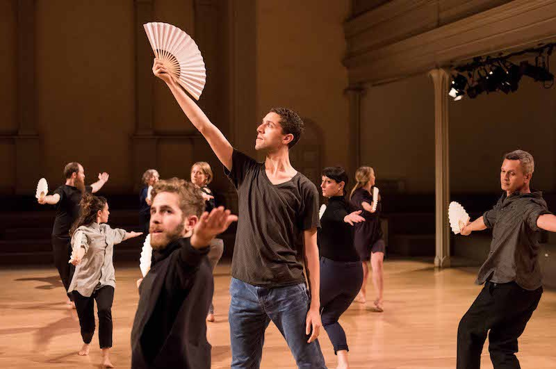 A cluster of dancers move independently with fans in their palms
