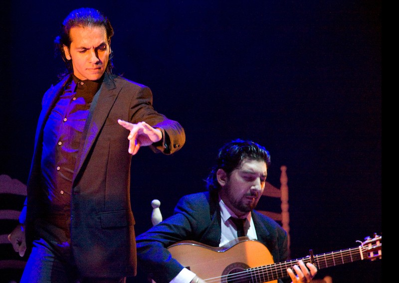 Farruquito onstage with a guitarist performs in an all black suit
