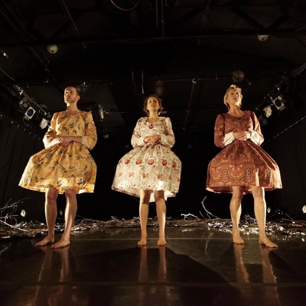 The three artists stand in front of the mylar and branch set in floral blouses and skirts