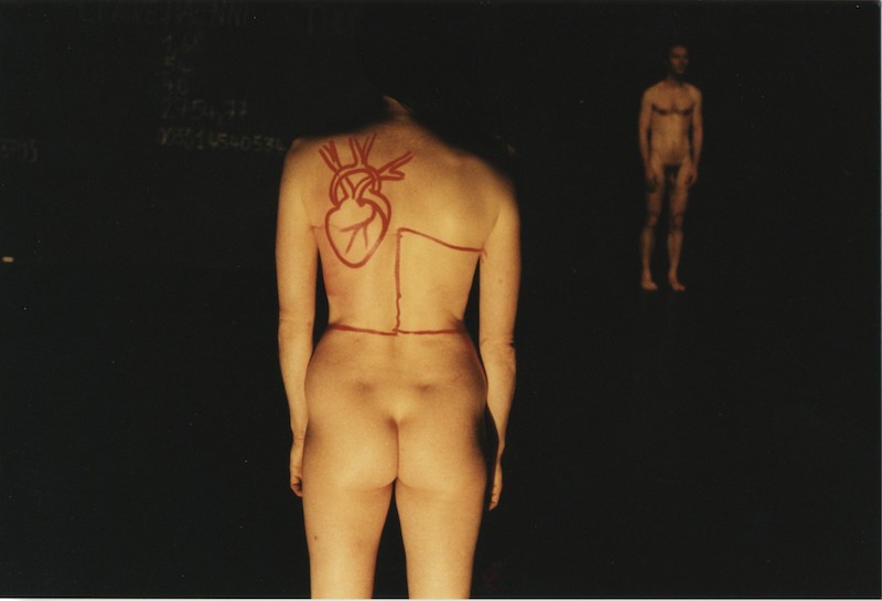 A woman's naked backside faces the audience. In red lipstick a drawing of a heart covers her shoulders.