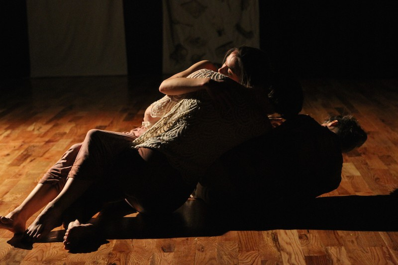 The three dancers are entangled on the floor in shadow