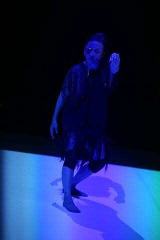 Koosil-ja in a black ensemble dancing in dim lighting giving off a sinister tone