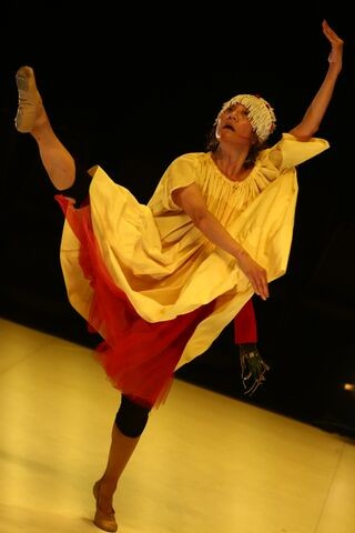 Wearing the yellow smock and fringe headpiece, Koolsil-ja extends her leg above her head