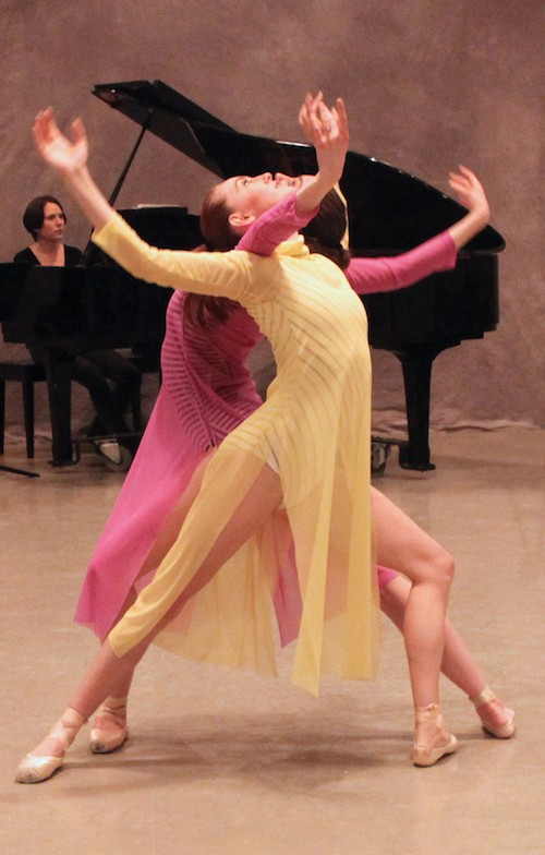 Two women lunge and arch their backs. Their faces look up to ceiling. A woman playing the piano is in the background.