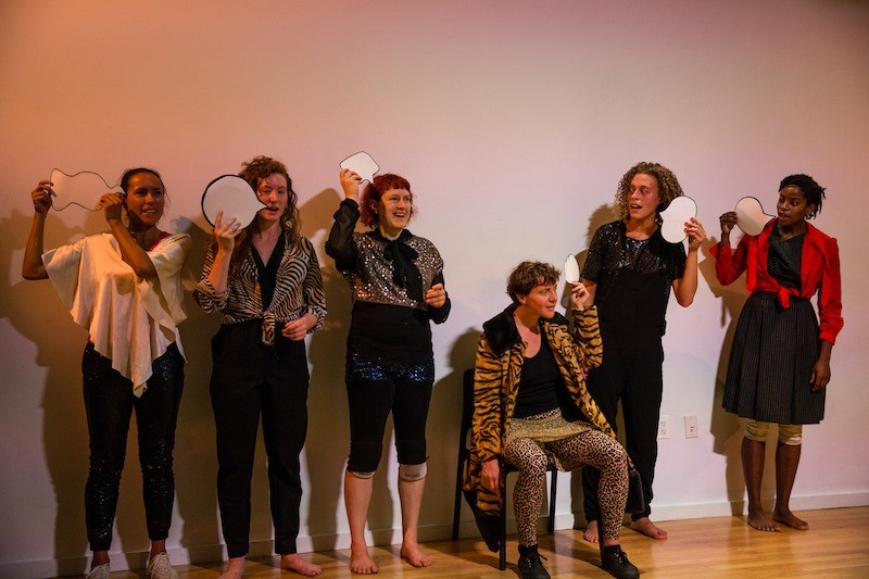 The cast, in wild animal prints and outlandish ensembles, hold up card board word bubbles