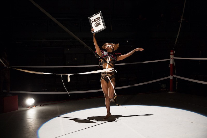 chipaumire holding a sign that says 'round one' in a boxing ring. Ropes encircle her stomach.
