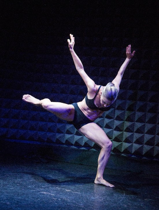 A female dancer in a bra top and shorts balances on one leg with her standing leg bent. Her torso and head face the floor as her arms extend behind her.