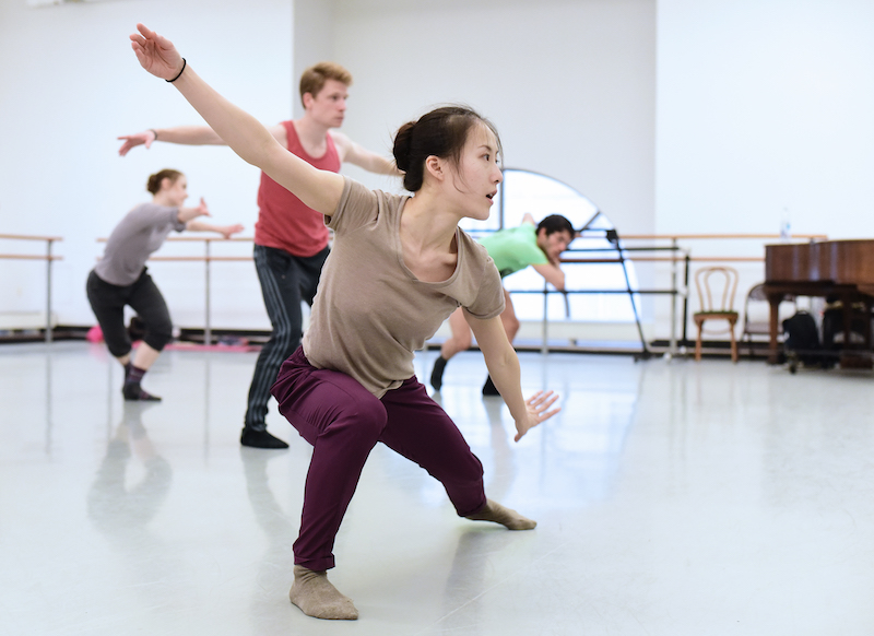 Yin Yue in a deep lunge while dancers behind her learn her steps in a white studio