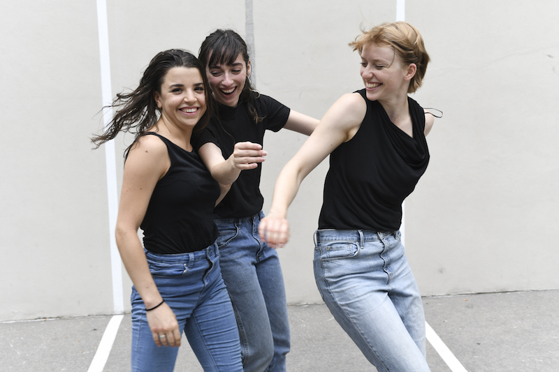 Three women smile wearing black tanks and jeans.