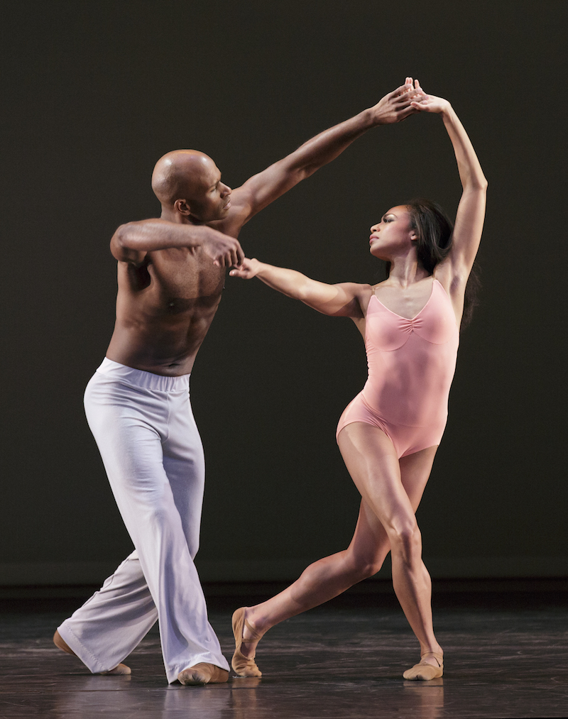 Linda Celeste Sims tenderly holds onto to her partner and husband's arms creating an arc with their arms