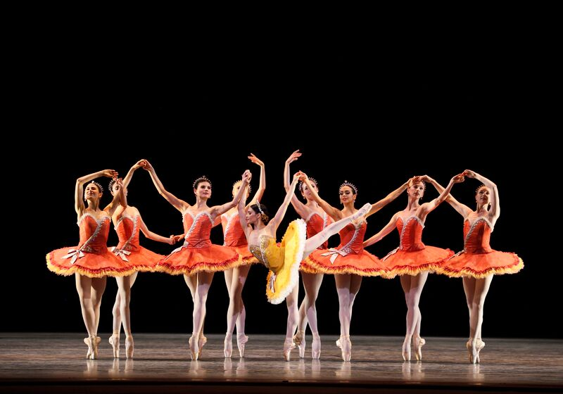 Soloist Sarah Lane in a bright yellow tutu strikes a high arabesque while the corps de ballet in orange tutus stand en pointe in the background