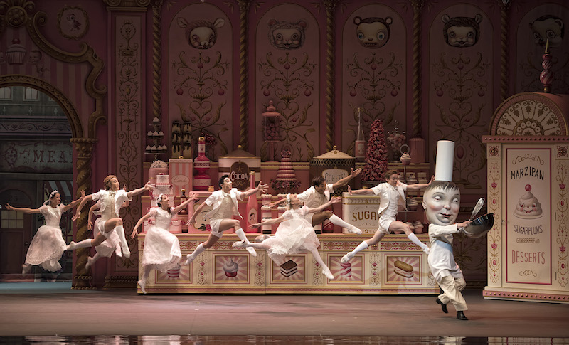 A group of young dancers dressed in white leap buoyantly in the air. A dancer in a larger-than-life chef masks teases them with sugary confections.