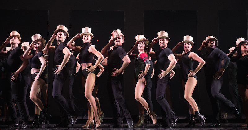 The company donned in black practice clothes and gold top hats strut in a straight line downstage
