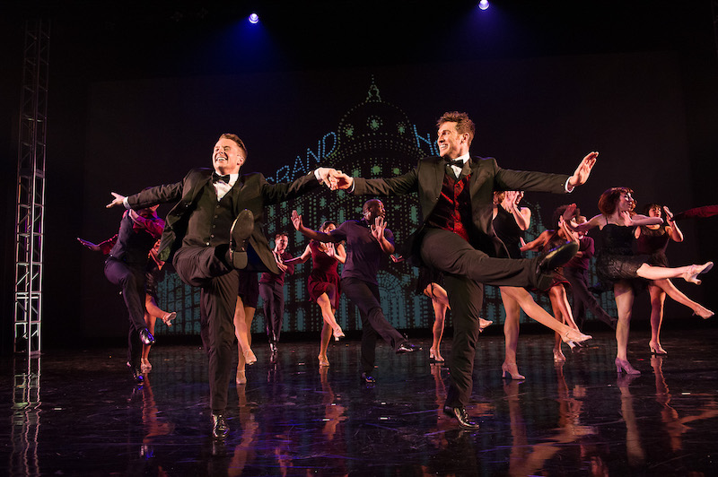 Two male dancers in bow ties, vests and tails link arms and kick enthusiastically with the chorus members behind them