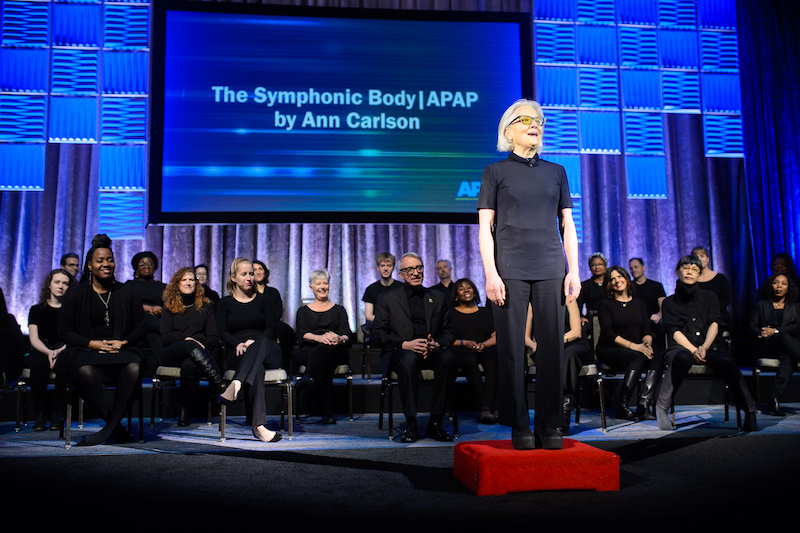 Ann Carlson, all in black, stands in front of her symphonic body chorus who are seated and also wearing black.
