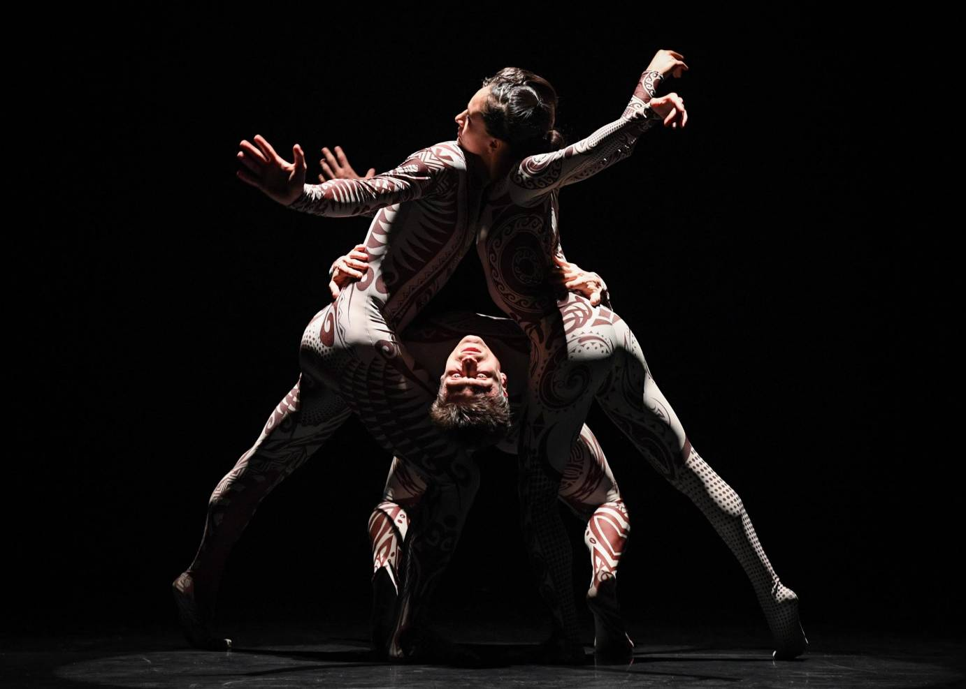 Three dancers form a triangle with their chests