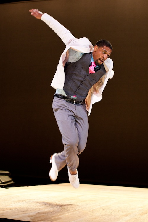 Tapper Jason Samuels Smith in a white blazer and colorful tip leaps into the air. His white tap shoes are off the ground.