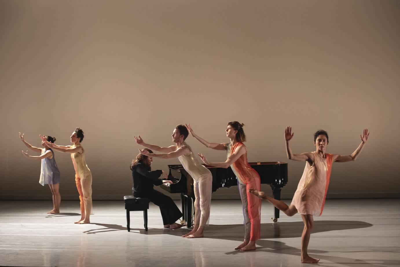 Dancers with curved arms gather around Simone Dinnerstein playing the piano