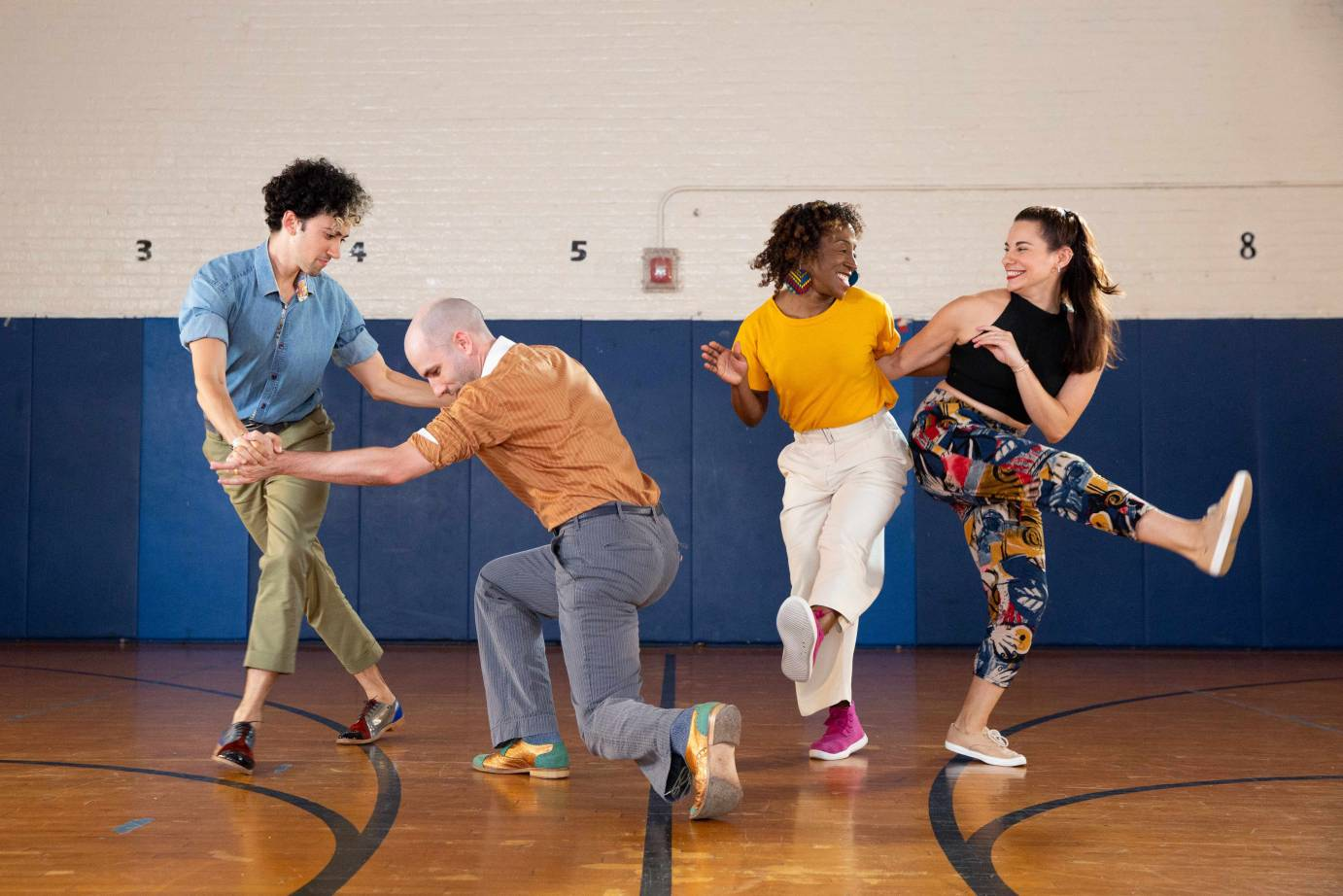 Two same-gender couples swing dance in brightly colored clothing