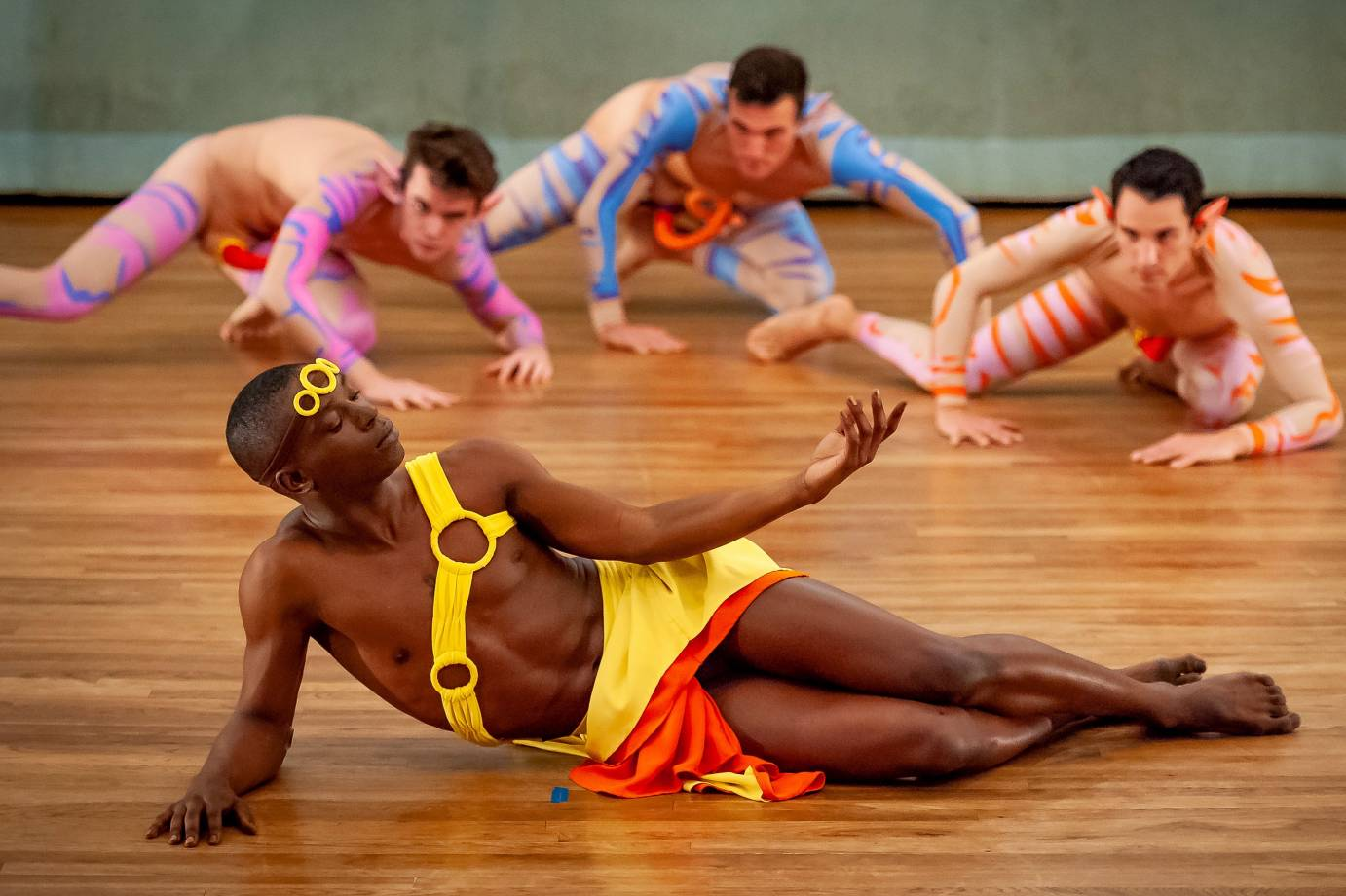 A man in a yellow tunic poses in front of three crawling dancers
