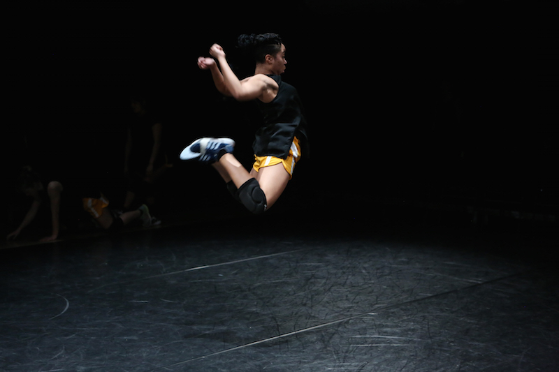 A woman jumps into the air kicking her legs behind her seat and arms swing to her sides. The view is in profile. She wears a black tank top, orange athletic shorts, knee pads and sneakers.