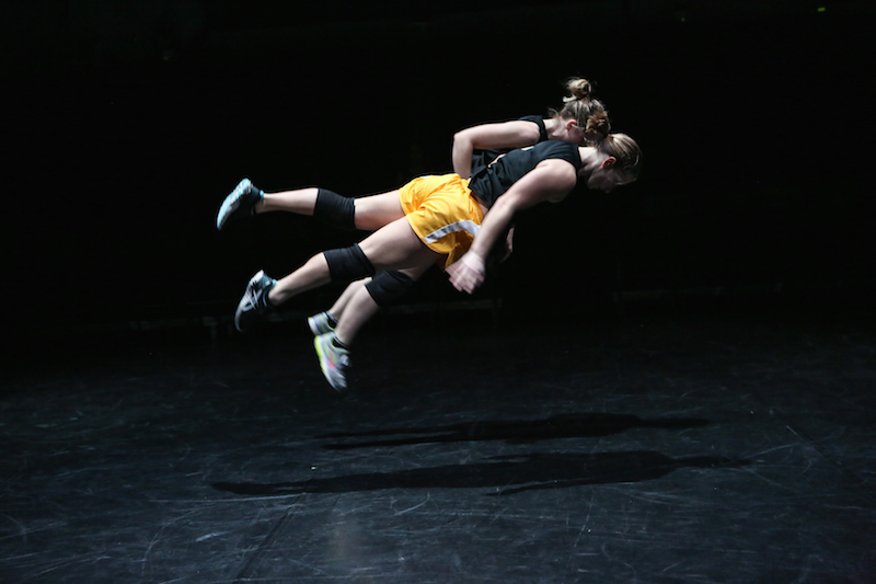 Two women are airborne parallel to the ground as if they were floating. Both women are wearing view is in profile. She wears a black tank top, orange athletic shorts, knee pads and sneakers.