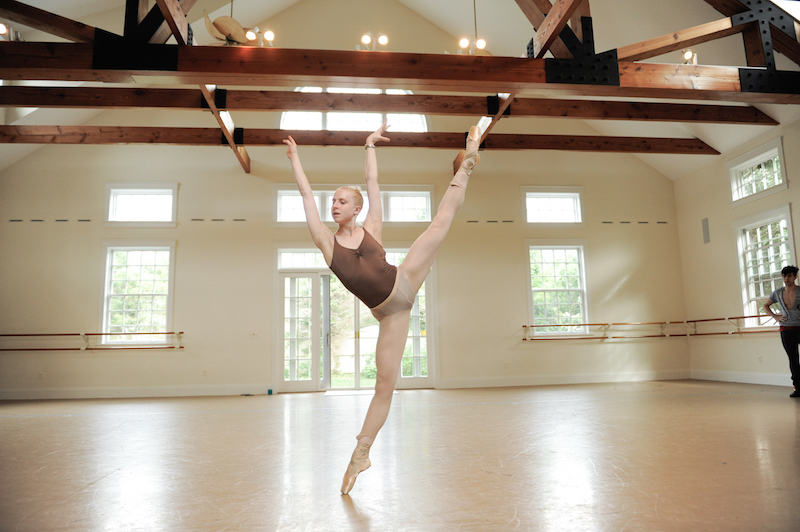 Woman on pointe lifts her leg high in the air