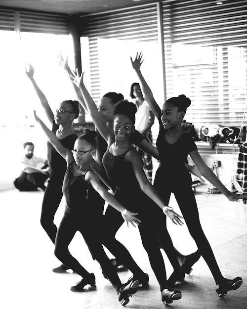 A group of young students in black tights, leos and tap shoes. They pose in a tight grouping with on foot extended out. Their arms splayed in a diagonal.