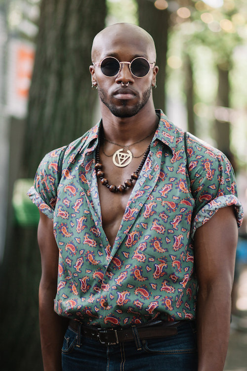 J. Bouey wears round wire rim sunglasses and pink and green patterned shirt.