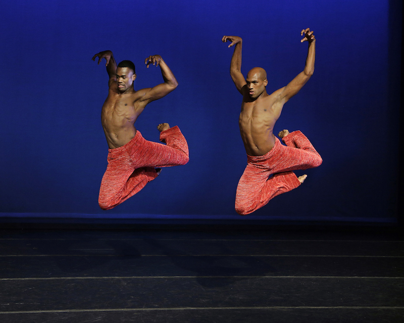 Two Ailey male dancers are in midair legs bent behind them