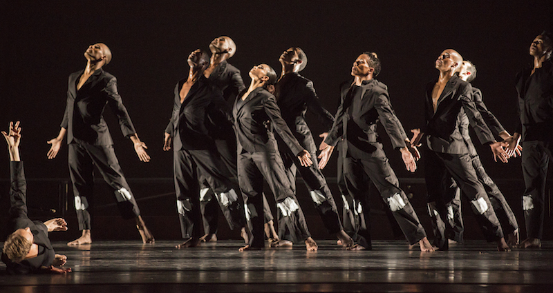Ailey dancers dress in black suits  have their palms open and heads tilted to the ceiling