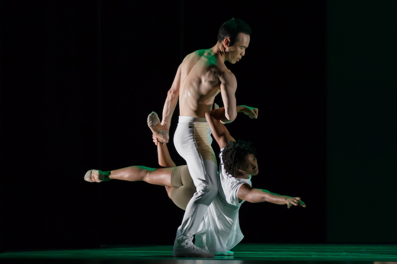 Kanji holds dancer Jacuelin Harris  between his legs. She is a few inches from the floor.